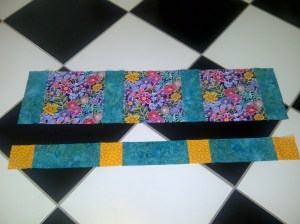The 3 x 3 inch squares attached to the 3 x 9 inch strips to make the alternating row. My floor is so handy to lay my quilts out on.