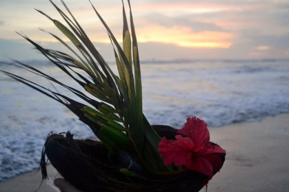 "My youngest who is traveling in Costa Rica made this token for her grandfather. She used ""half of a rotting coconut to symbolize death, a rock washed up on the beach to represent the earth, a piece of palm to represent our family and home, and a flower for life."" And then she sent it out sea."